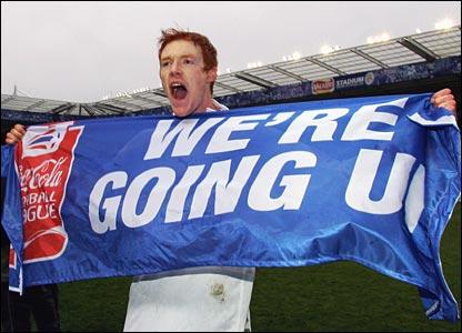 Reading striker Dave Kitson holds up banner in celebration