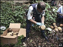 A UN police officer examines the discovered skulls in Haiti
