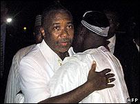 Charles Taylor (left) embraces Nigerian President Olusegun Obasanjo in Abuja in 2003