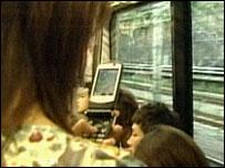 Mujer sostiene un celular en un autobús