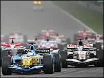 Giancarlo Fisichella's Renault leads the Honda of Jenson Button into the first corner at the Malaysian Grand Prix