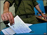 Un soldado deposita su voto