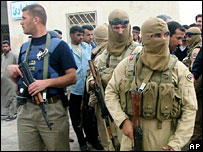 Iraqi police and military guard the site of a suicide bombing at a police station in Haswa