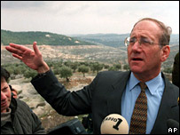 With the disputed hill Har Homa in the background, then Jerusalem Mayor Ehud Olmert speaks to reporters during a press conference in 1997