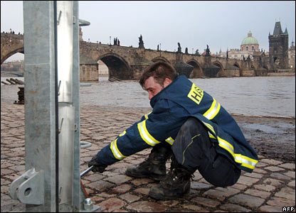 A fireman fixes a metal post to prevent water spilling into streets in the medieval Kampa district