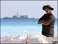 Mexican soldier on patrol in Cancun as navy ship passes