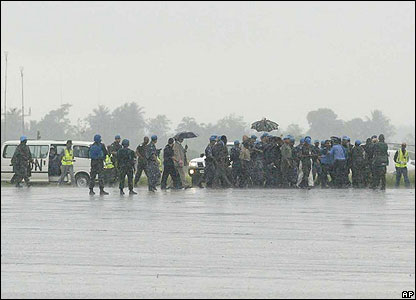 Charles Taylor walks across the tarmac at an airport in Monrovia, Liberia, in the rain