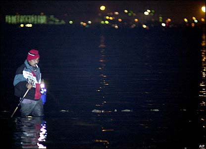 A man searches the water using a torch