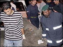 Rescuers carry a body in Bahrain