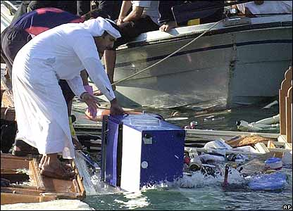 Rescue crews recover a cooler from the debris