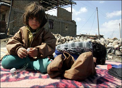 Two young girls sit on a rug surrounded by rubble
