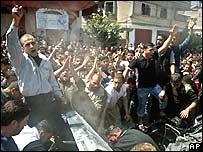 Palestinians surround the wreckage of Khalil al-Quqa's car