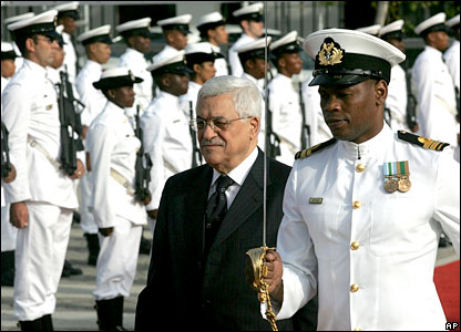 Palestinian leader Mahmoud Abbas walks with a naval officer during a welcome ceremony in South Africa during a visit.