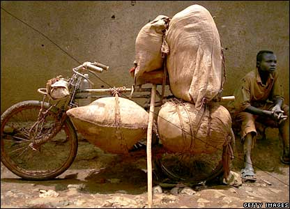 A boy rests next to his battered bicycle in the gold mining town of Mongbwalu