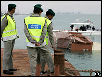 Bahraini police by the wreckage of the capsized boat