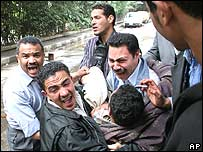 An injured man is carried from the Wafd headquarters