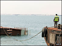 A Bahraini policeman looks at the wreckage of the capsized boat
