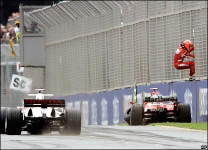 Michael Schumacher climbs through the debris fencing back to the pits after crashing in Melbourne