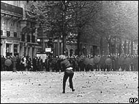 A demonstrator hurls a stone at riot police in Paris in May 1968