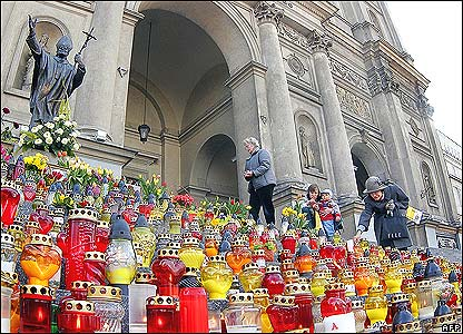 People lay flowers and light candles at a Warsaw church