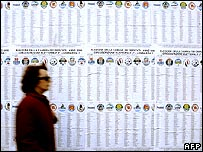 Woman walks past posters listing political parties