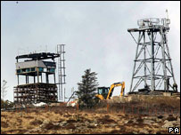 Digger on hill among watchtowers being dismantled