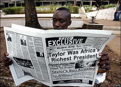 A journalist reads a newspaper at the entrance to the court in Freetown