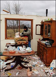 A woman tries to salvage dishes from a house destroyed by a tornado in Missouri