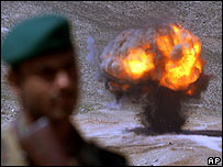 An Afghan soldier stands guard as anti-personnel mines are exploded