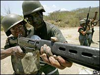 A territorial guard member, left, is helped by a Venezuelan army officer to aim a FALassault rifle