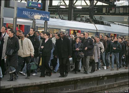 Commuters wait to board a train at a Paris mainline station