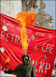 A student blows a flame at the start of a protest in Paris in front of a banner calling for the law to be withdrawn.