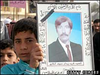 An Iraqi boy holds a photograph of a man killed in Dujail