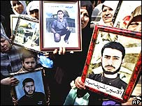 Palestinians in Gaza City hold pictures of relatives being held in Israeli jails