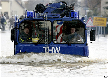 German rescuers drive through a flooded street