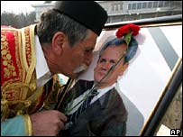 A Milosevic supporter kisses a portrait of the former leader