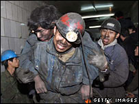 Rescuers assist a miner after he was trapped following a blast at a Chinese coal mine