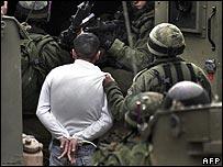 Israeli troops arrest a Palestinian in Nablus