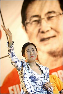 Satomi Kataoka waves to Fujimori supporters at a rally in Lima against a poster of Alberto Fujimori in the background