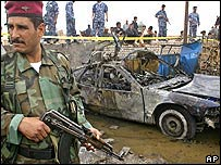 Iraqi guard next to the wreckage of the bombed car