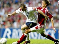 England footballer Wayne Rooney (left) is tackled by Daniel Agger of Denmark