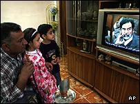 An Iraqi family watches the trial of former dictator Saddam Hussein on state television