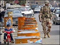 A boy plays with his tricycle as an Iraqi soldier watches the flow of cars in Baghdad