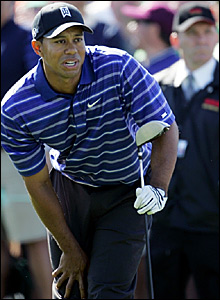 Tiger Woods anxiously watches his drive on the first