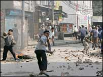Protesters throw stones during a rally in Kathmandu