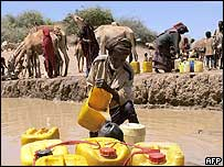 Somali man fills bottles with muddy water