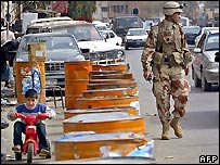 A boy and a soldier in an Iraqi street
