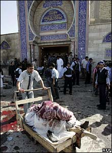 A man pushes a cart laden with dead bodies outside the mosque
