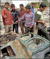 Children look at the wreckage of a US vehicle in Ramadi