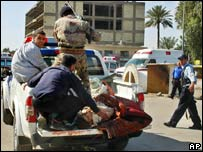 Injured are taken by truck from the scene of the bomb blasts at a mosque in Baghdad